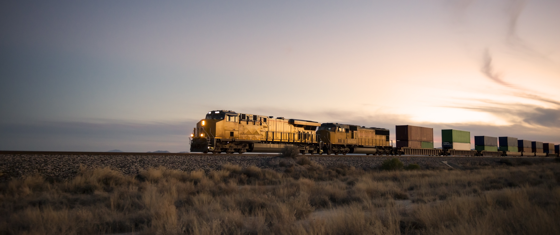 Locomotive rolling through plains at sunset